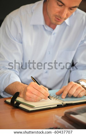 Businessman writing down in an organizer