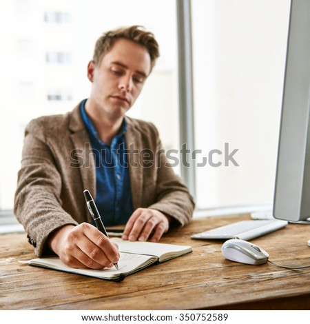 Businessman writing down some important notes in his office diary at his desk while at work
