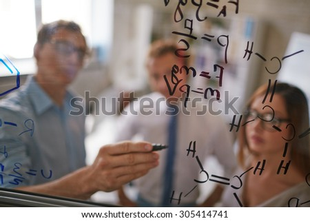 Businessman writing formulae on transparent board