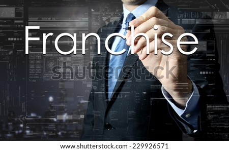 Businessman writing Franchise on virtual screen behind the back of the businessman one can see the city behind the window - stock photo