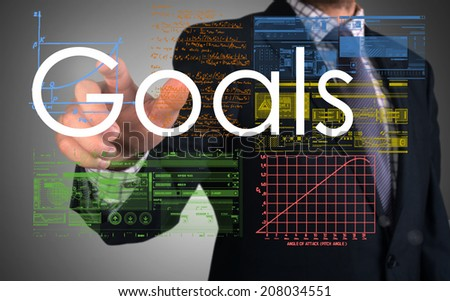 businessman writing Goals and drawing some sketches and charts - stock photo