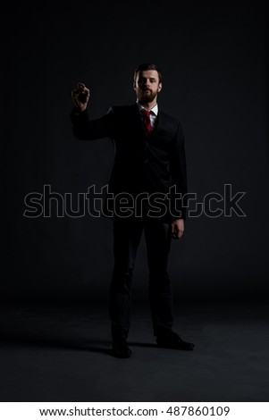 Businessman writing imaginary text over black background. Business and office concept.