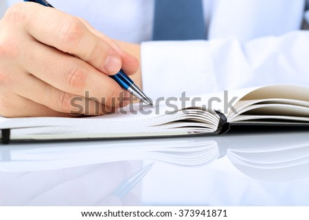 businessman writing in a notebook while sitting at a  his desk - stock photo
