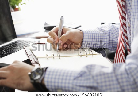 Businessman writing in his calendar - stock photo