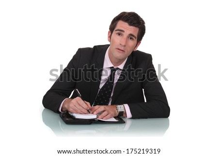 Businessman writing in his diary - stock photo