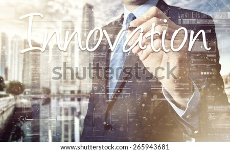 businessman writing innovation and drawing graphs and diagrams - stock photo