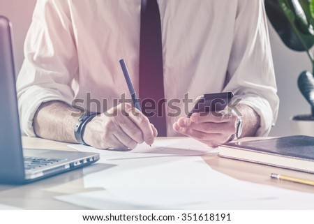 Businessman writing notes from mobile phone, working overtime at office desk, multitasking and project deadline concept, retro toned image, selective focus - stock photo