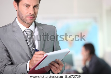 Businessman writing on a clipboard - stock photo