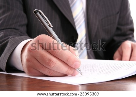 businessman writing on a form using his pen