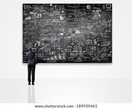 businessman writing on blackboard with business plan - stock photo