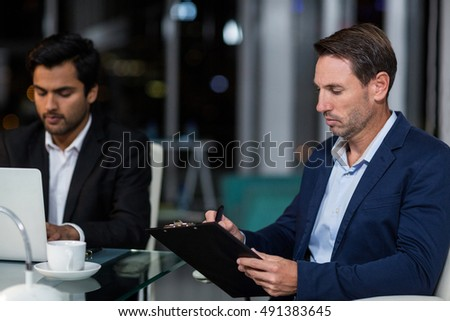 Businessman writing on clipboard in the office