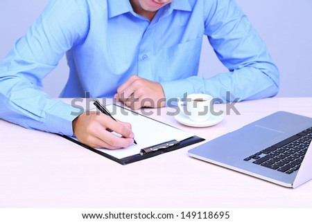 Businessman writing on document in office close-up - stock photo