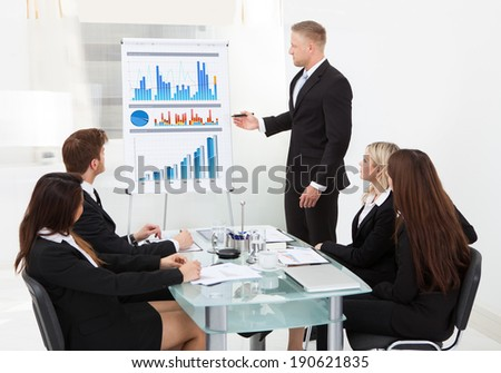 Businessman writing on flipchart while giving presentation to colleagues in office - stock photo