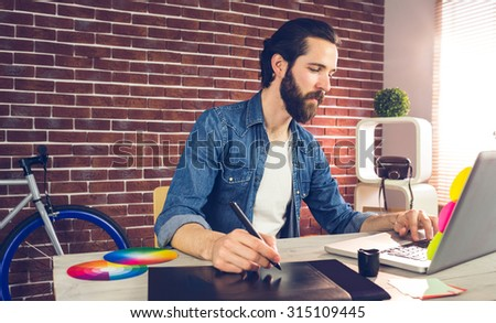 Businessman writing on graphic tablet while using laptop in creative office - stock photo