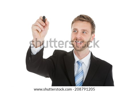 Businessman writing on invisible screen with marker over white background - stock photo