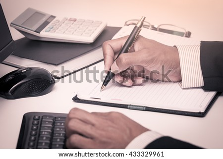 Businessman writing on notebook with pen and working in the office in vintage color tone