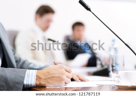 Businessman writing on paper notes, to communicate with colleagues in the background