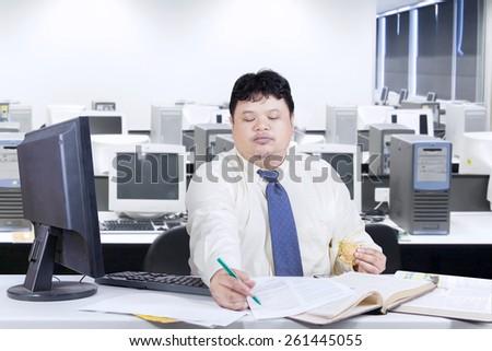 Businessman writing on the document while holding a burger, shot in the office room - stock photo