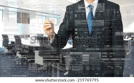 businessman writing on transparent board with office in background - stock photo