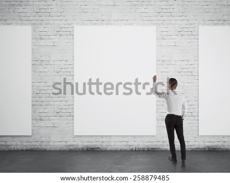 Businessman writing or drawing something on white blank board over brick wall background from back - stock photo