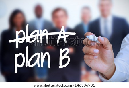 Businessman writing plan B with a marker in front of a business team - stock photo