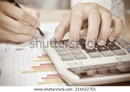 Businessman writing report and calculate on the desk in office. - stock photo