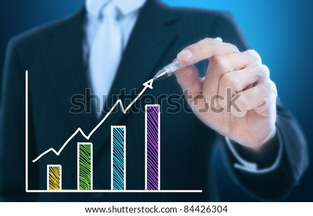 businessman writing rising graph ,blue background