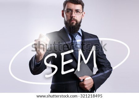 """Businessman writing """"SEM"""" with marker on transparent board. - stock photo"""