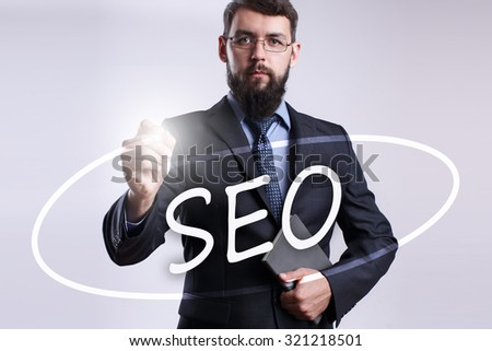 """Businessman writing """"SEO"""" with marker on transparent board. - stock photo"""