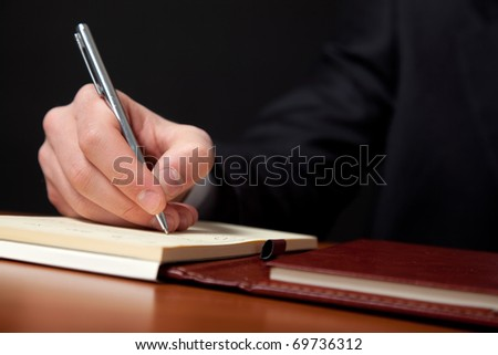 Businessman writing some documents on a wood desk in low light - stock photo