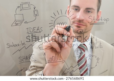 Businessman Writing Start Up Planning With Marker On Glass - stock photo