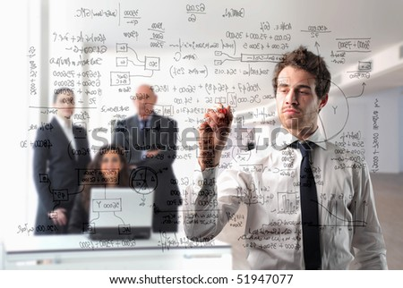 Businessman writing statistics with group of business people on the background