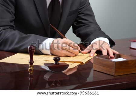 Businessman writing testament at notary public office - stock photo