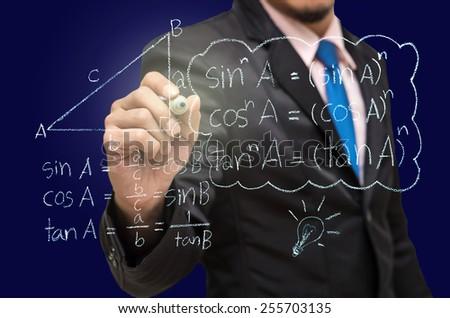 Businessman writing the mathematics formulas on a blackboard - stock photo