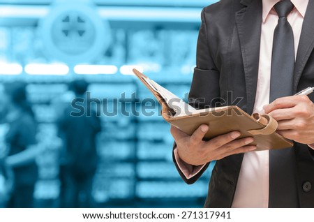 Businessman writing the note book on Abstract blurred photo of book store with people background,blue color background - stock photo