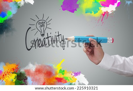 Businessman writing the word creativity and painting abstract colorful design on gray background concept for business idea, imagination and inspiration - stock photo