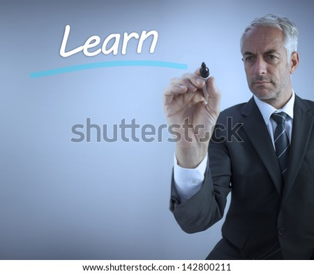 Businessman writing the word learn with a marker - stock photo