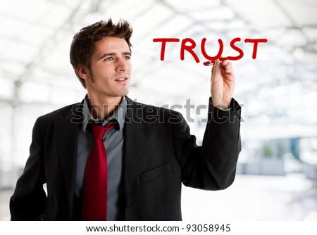 Businessman writing the world Trust on the screen