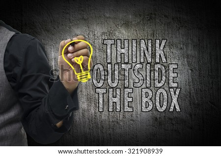 Businessman writing Think outside the box - stock photo