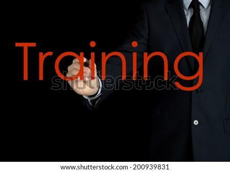 businessman writing training on black background - stock photo