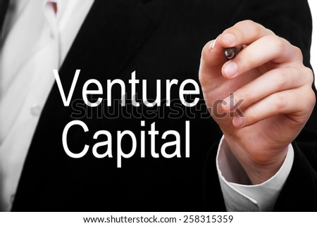 Businessman writing Venture Capital concept on transparent board - stock photo