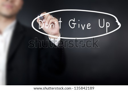 Businessman writing word don't give up - stock photo