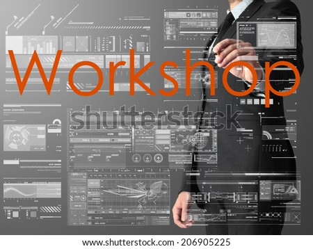 businessman writing Workshop and drawing graphs and diagrams on grey background - stock photo