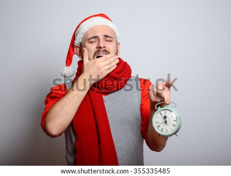 Businessman yawning stretching after sleeping with an alarm clock. Happy man wearing Santa hat on New Year's corporate parties. Studio photo, isolated - stock photo