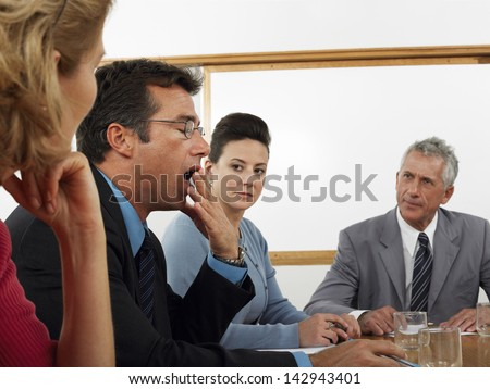 Businessman yawning with colleagues looking at him during meeting at conference room - stock photo