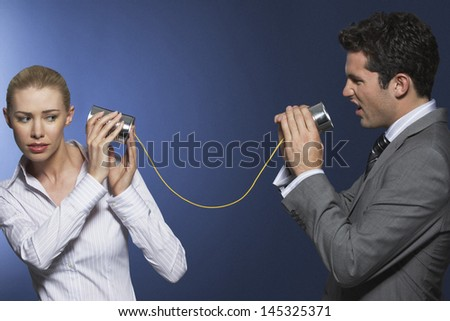Businessman yelling at female colleague through tin can phone against blue background - stock photo