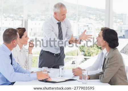 Businessman yelling at his team in the office - stock photo