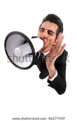 Businessman yelling into a megaphone - stock photo