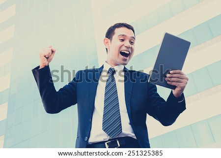 Businessman yelling & raising his fist while looking at tablet pc - vintage & retro style color effect - stock photo