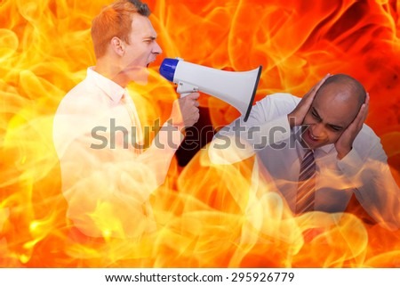 Businessman yelling with a megaphone at his colleague against fire - stock photo